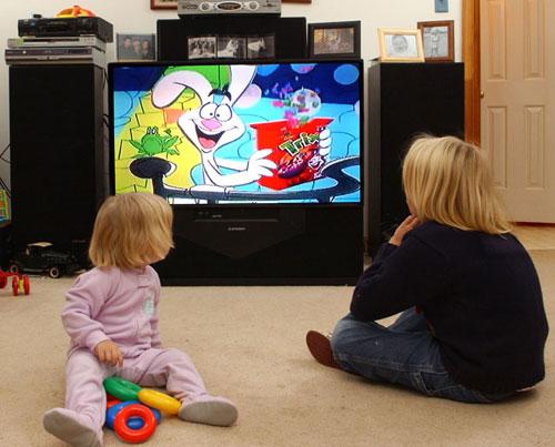 Deca pored upaljenog televizora